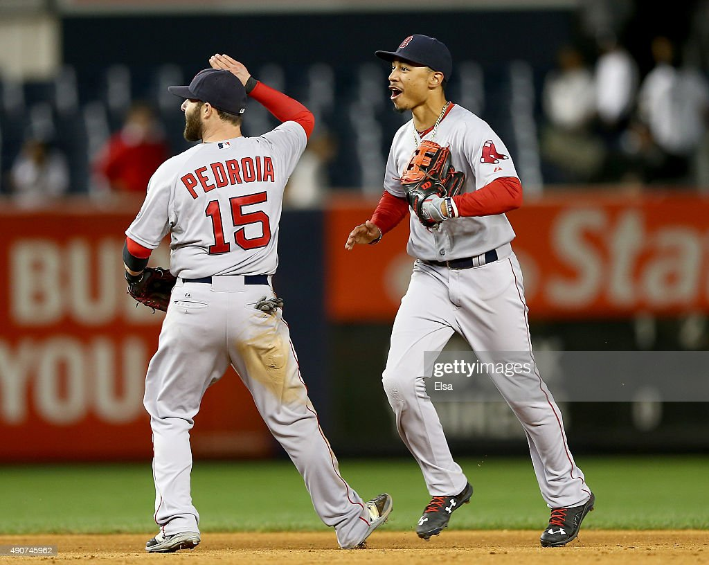 Dustin Pedroia #15 and Mookie Betts #50 of the Boston Red Sox celebrate the win over the New York Yankees on September 30, 2015 at Yankee Stadium in the Bronx borough of New York City.The Boston Red Sox defeated the New York Yankees 9-5 in 11 innings.