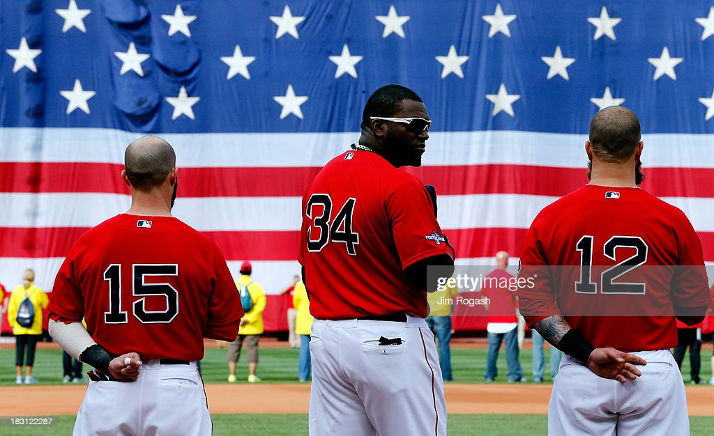 Dustin Pedroia #15, David Ortiz #34, and Mike Napoli #12 of the Boston Red Sox look on during the national anthem before Game One of the American League Division Series against the Tampa Bay Rays at Fenway Park on October 4, 2013 in Boston, Massachusetts.