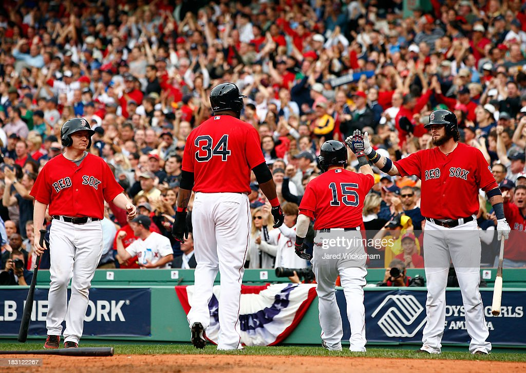 Dustin Pedroia #15, Jarrod Saltalamacchia #39, and David Ortiz #34 of the Boston Red Sox celebrate a run against the Tampa Bay Rays during Game One of the American League Division Series at Fenway Park on October 4, 2013 in Boston, Massachusetts.