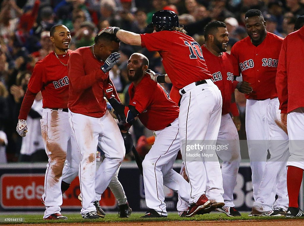 Dustin Pedroia #15, Mookie Betts #50 and Ryan Hanigan #10 celebrate with Xander Bogaerts #2 of the Boston Red Sox after he hit a single during the ninth inning allowing Mike Napoli #12 to score the game winning run against the Baltimore Orioles at Fenway Park on April 17, 2015 in Boston, Massachusetts. The Red Sox defeat the Orioles 3-2.
