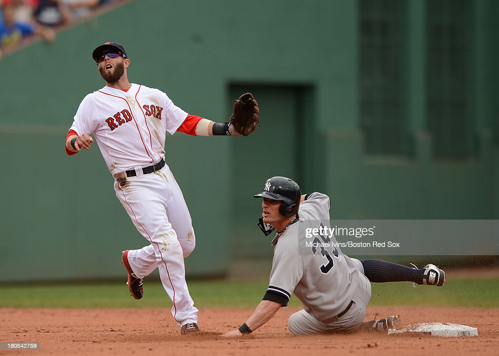 Dustin Pedroia #15 of the Boston Red Sox and Brendan Ryan #35 of the New York Yankees watch after a throw by Pedroia came short of completing a double play in the fourth inning on September 14, 2013 at Fenway Park in Boston Massachusetts.
