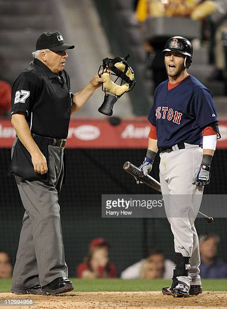 Dustin Pedroia of the Boston Red Sox argues a called strikeout at the plate with home plate unpire Larry Vanover against the Los Angeles Angels of...