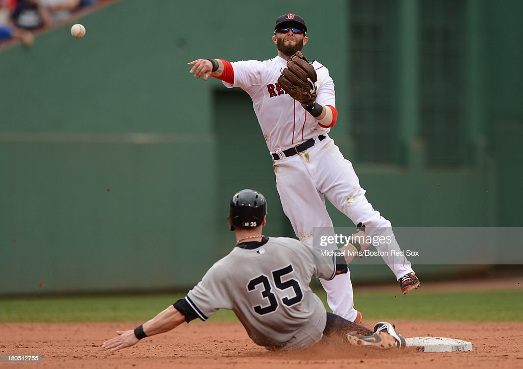 Dustin Pedroia #15 of the Boston Red Sox attempts to complete a double play over the head of Brendan Ryan #35 of the New York Yankees during the fourth inning on September 14, 2013 at Fenway Park in Boston Massachusetts.