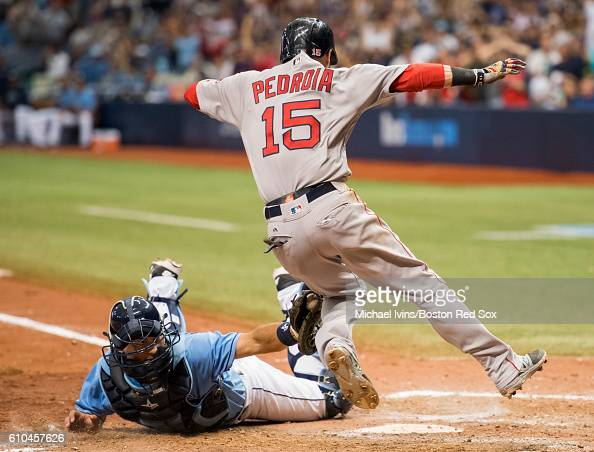 Dustin Pedroia of the Boston Red Sox avoids the tag of Curt Casali of the Tampa Bay Rays to score a goahead run in the tenth inning on September 25...