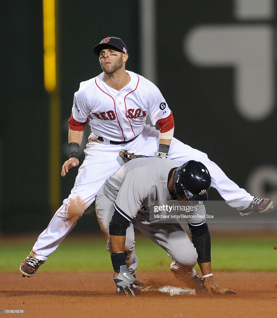 Dustin Pedroia #15 of the Boston Red Sox completes a double play over Chris Dickerson #60 of the New York Yankees in the eighth inning on September 11, 2012 at Fenway Park in Boston, Massachusetts.