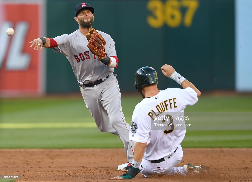 Dustin Pedroia #15 of the Boston Red Sox completes the double-play by getting his throw off over the top of Trevor Plouffe #3 of the Oakland Athletics in the bottom of the second inning at Oakland Alameda Coliseum on May 19, 2017 in Oakland, California.