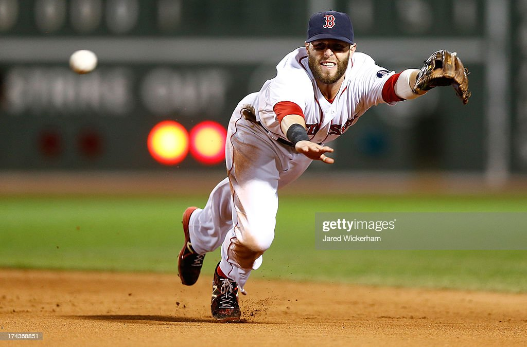Dustin Pedroia #15 of the Boston Red Sox dives but misses catching a line drive against the Tampa Bay Rays during the game on July 24, 2013 at Fenway Park in Boston, Massachusetts.