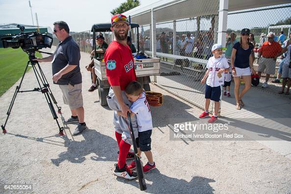 Dustin Pedroia of the Boston Red Sox gets a hug from his son Cole during a break in practice on February 18 2017 at jetBlue Park in Fort Myers Florida