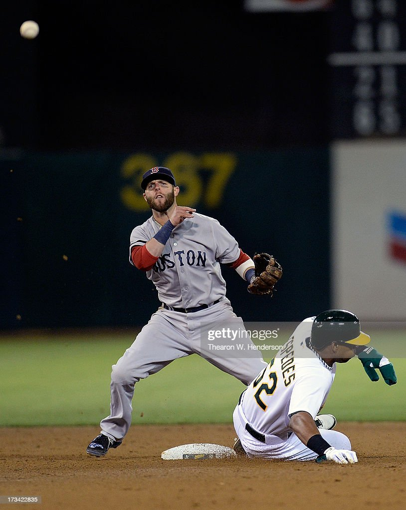 Dustin Pedroia #15 of the Boston Red Sox gets his throw off to complete the double-play as Yoenis Cespedes #52 of the Oakland Athletics slides into second base in the eighth inning at O.co Coliseum on July 13, 2013 in Oakland, California.