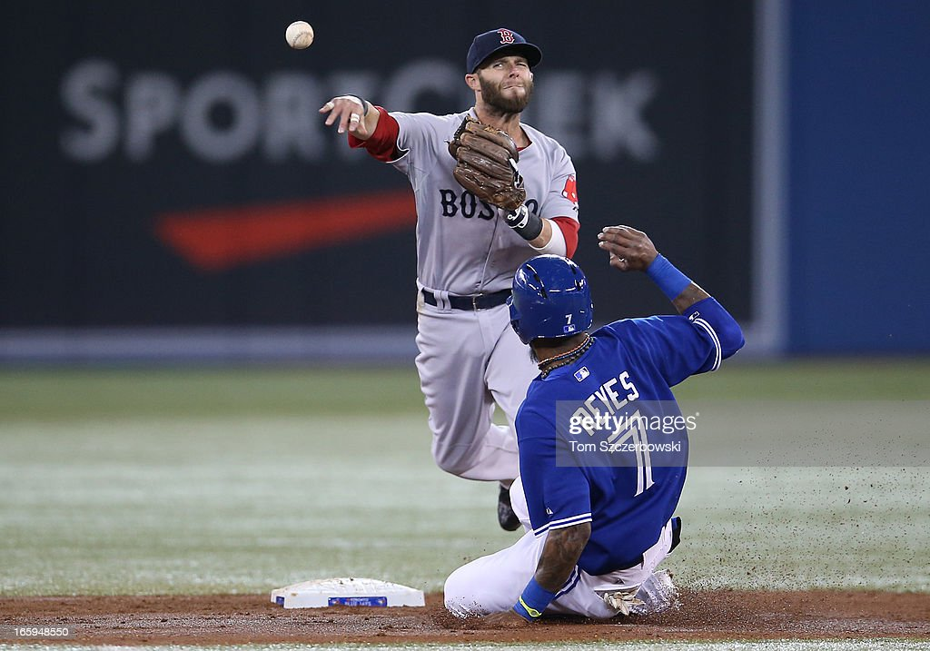 Dustin Pedroia #15 of the Boston Red Sox gets the force out at second base in the third inning as Jose Reyes #7 of the Toronto Blue Jays slides during MLB game action on April 7, 2013 at Rogers Centre in Toronto, Ontario, Canada.