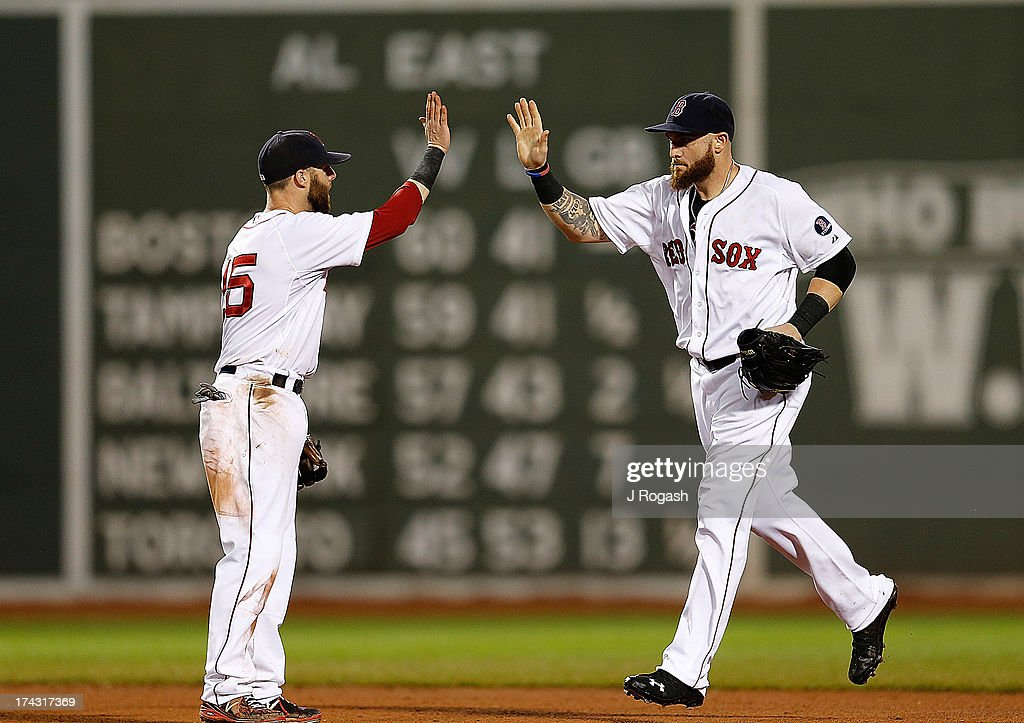 Dustin Pedroia #15 of the Boston Red Sox greets Jonny Gomes #5 to celebrate a win over the Tampa Bay Rays at Fenway Park on July 23, 2013 in Boston, Massachusetts.