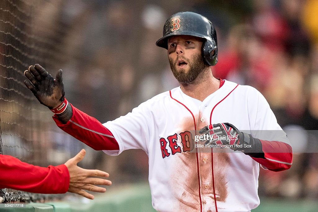 Dustin Pedroia #15 of the Boston Red Sox high fives teammates after scoring during the first inning of a game against the Colorado Rockies on May 24, 2016 at Fenway Park in Boston, Massachusetts.