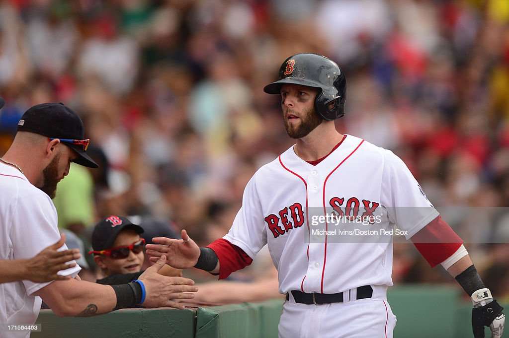 Dustin Pedroia #15 of the Boston Red Sox is congratulated after scoring against the Colorado Rockies in the third inning on June 26, 2013 at Fenway Park in Boston, Massachusetts.