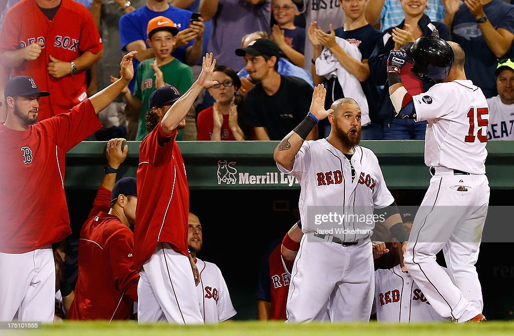 Dustin Pedroia #15 of the Boston Red Sox is congratulated by Jonny Gomes #5 of the Boston Red Sox in the dugout after hitting a two-run home run in the 7th inning against the Seattle Mariners during the game on July 31, 2013 at Fenway Park in Boston, Massachusetts.