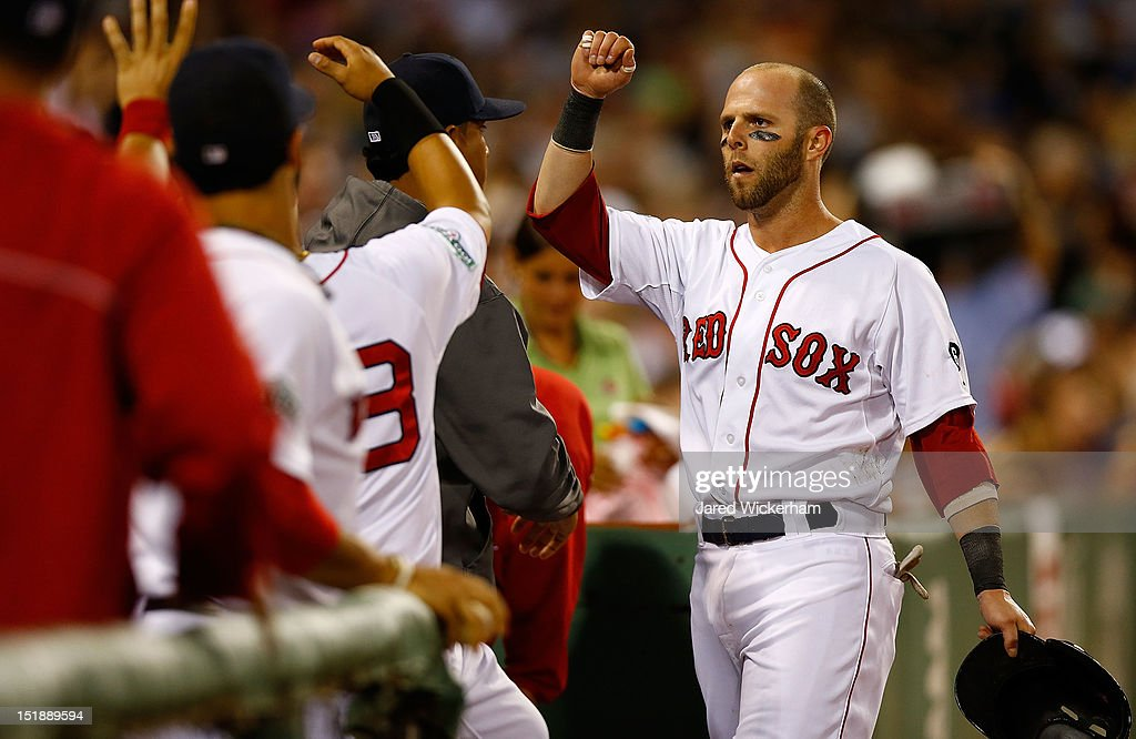 Dustin Pedroia #15 of the Boston Red Sox is congratulated by teammates in the dugout after hitting a solo home run against the New York Yankees in the fourth inning during the game on September 12, 2012 at Fenway Park in Boston, Massachusetts.
