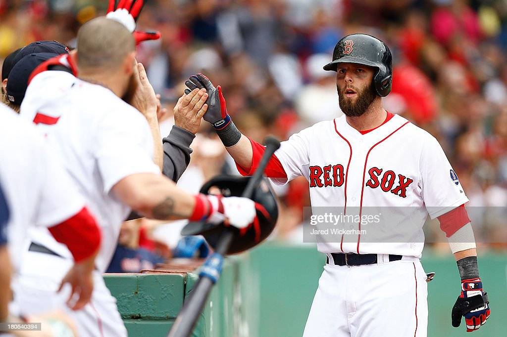Dustin Pedroia #15 of the Boston Red Sox is congratulated by teammates after scoring against the New York Yankees during the game on September 14, 2013 at Fenway Park in Boston, Massachusetts.