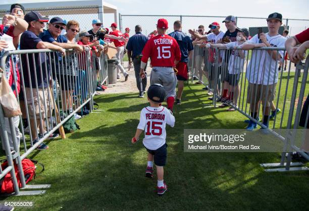 Dustin Pedroia of the Boston Red Sox is followed by his son Brooks as he runs to a practice field on February 18 2017 at jetBlue Park in Fort Myers...