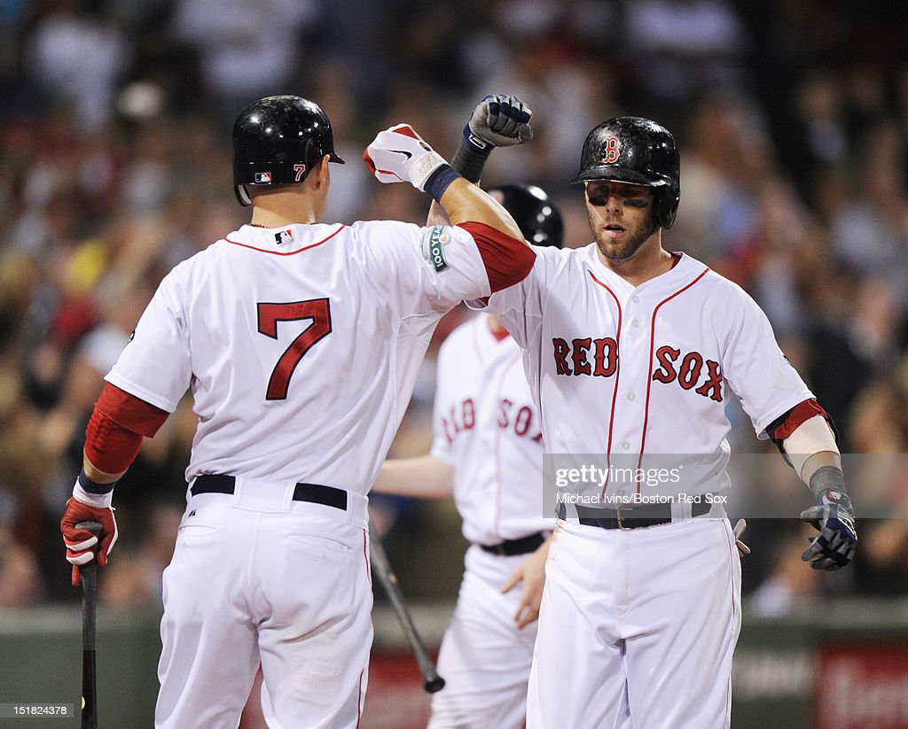 Dustin Pedroia #15 of the Boston Red Sox is greeted by Cody Ross #7 after hitting a home run against the New York Yankees in the sixth inning on September 11, 2012 at Fenway Park in Boston, Massachusetts.
