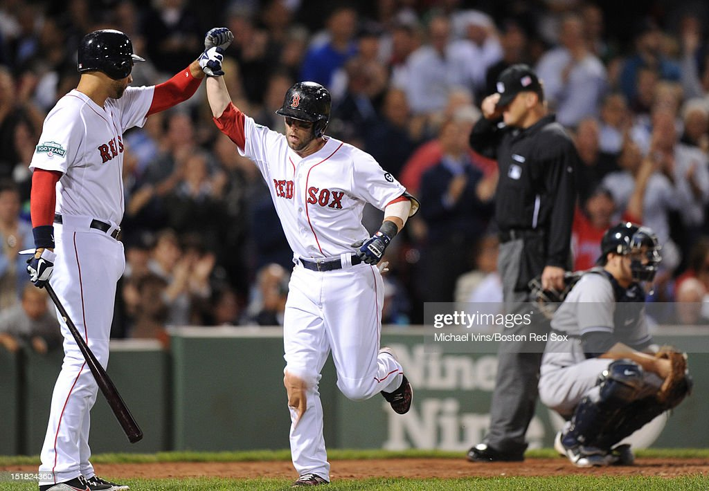 Dustin Pedroia #15 of the Boston Red Sox is greeted by James Loney #22 after hitting a home run against the New York Yankees in the sixth inning on September 11, 2012 at Fenway Park in Boston, Massachusetts.