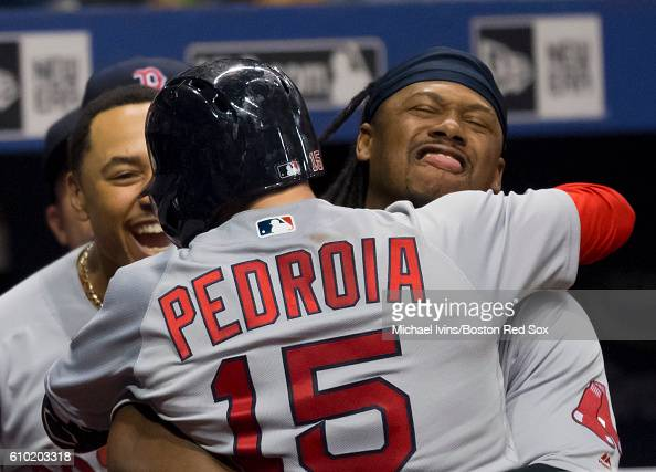 Dustin Pedroia of the Boston Red Sox is hugged by Hanley Ramirez after hitting a grand slam against the Tampa Bay Rays in the seventh inning on...