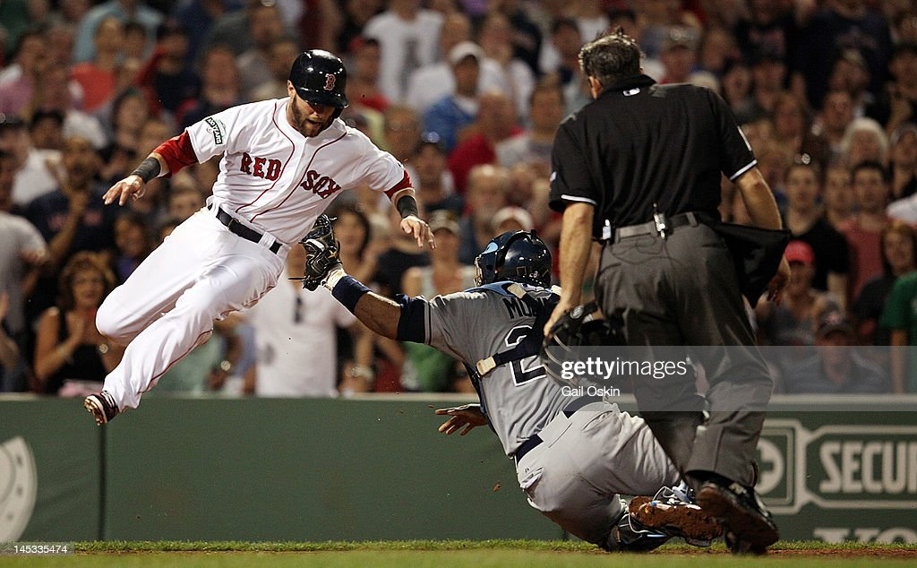 Dustin Pedroia #15 of the Boston Red Sox is tagged out at home by Jose Molina #28 of the Tampa Bay Rays in the sixth inning at Fenway Park on May 26, 2012 in Boston, Massachusetts.