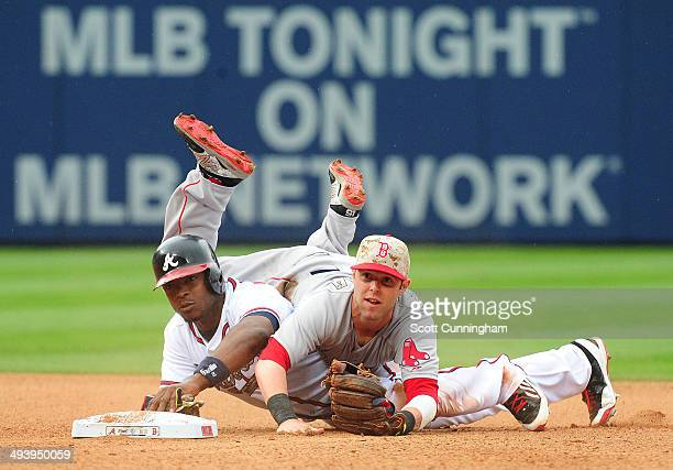 Dustin Pedroia of the Boston Red Sox is upended after turning a 6th inning double play against Justin Upton of the Atlanta Braves at Turner Field on...