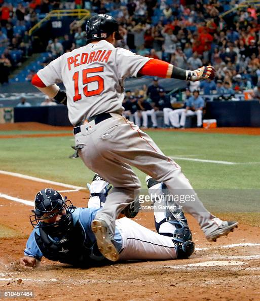 Dustin Pedroia of the Boston Red Sox jumps to avoid the tag of Luke Maile of the Tampa Bay Rays at home plate in the tenth inning to score the...