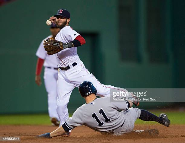Dustin Pedroia of the Boston Red Sox mishandles the ball while attempting to finish a double play against Brett Gardner of the New York Yankees in...