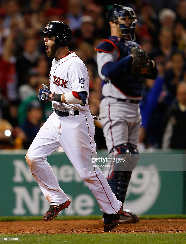Dustin Pedroia #15 of the Boston Red Sox reacts after he connected for a home run in the 8th inning as Joe Mauer #7 of the Minnesota Twins looks away at Fenway Park on May 6, 2013 in Boston, Massachusetts.
