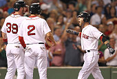 Dustin Pedroia of the Boston Red Sox reacts after he hit a threerun home run with teammates Jarrod Saltalamacchia of the Boston Red Sox and Jacoby...