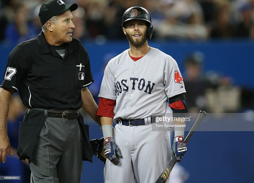 Dustin Pedroia #15 of the Boston Red Sox reacts after he was called out on a check swing appeal in the sixth inning during MLB game action as home plate umpire John Hirschbeck #17 looks on against the Toronto Blue Jays on April 6, 2013 at Rogers Centre in Toronto, Ontario, Canada.