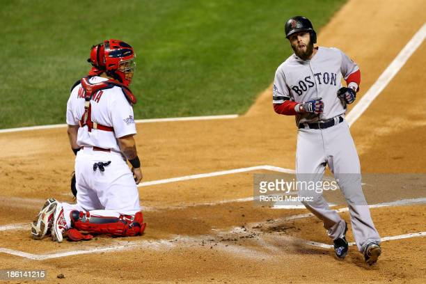 Dustin Pedroia of the Boston Red Sox scores on a double by David Ortiz in the first inning as Yadier Molina of the St Louis Cardinals looks on during...