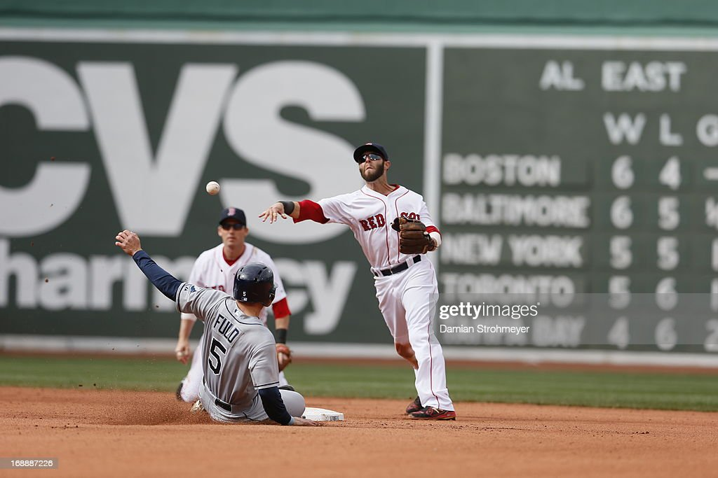 Dustin Pedroia #15 of the Boston Red Sox throws to first base as Sam Fuld #5 of the Tampa Bay Rays slides into second base during the game between the Tampa Bay Rays and the Boston Red Sox on Sunday, April 14, 2013 at Fenway Park in Boston, Massachusetts.
