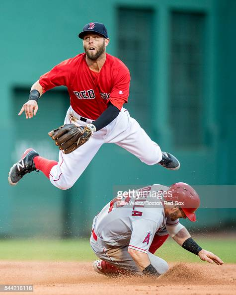 Dustin Pedroia of the Boston Red Sox turns a double play as Johnny Giovotella of the Los Angeles Angels of Anaheim slides during the second inning of...