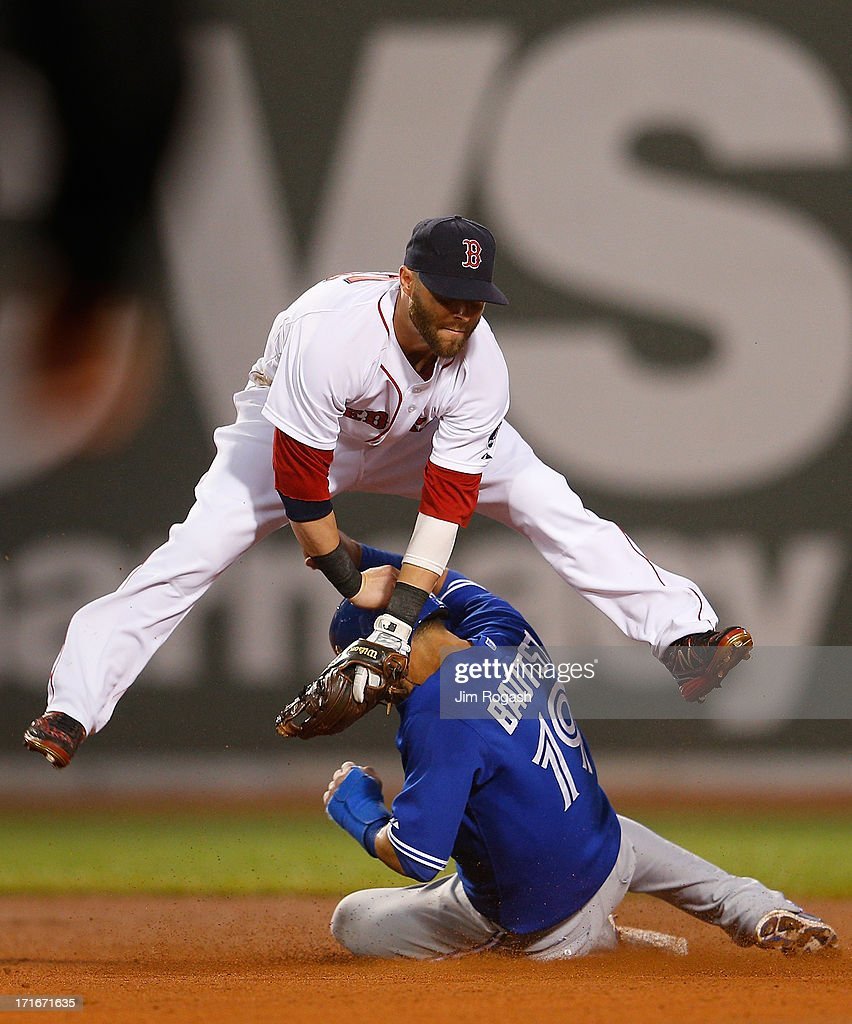 Dustin Pedroia #15 of the Boston Red Sox turns a double play as Jose Bautista #19 of the Toronto Blue Jays slides late in to second base in the 4th inning at Fenway Park on June 27, 2013 in Boston, Massachusetts.