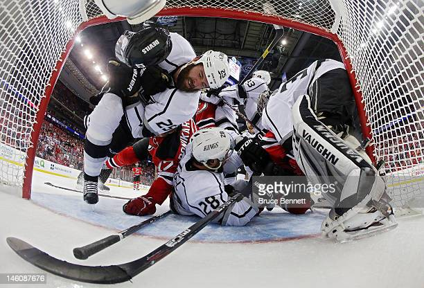 Dustin Penner Jarret Stoll and Jonathan Quick of the Los Angeles Kings pile up in front of the goal against Ilya Kovalchuk and Adam Henrique of the...