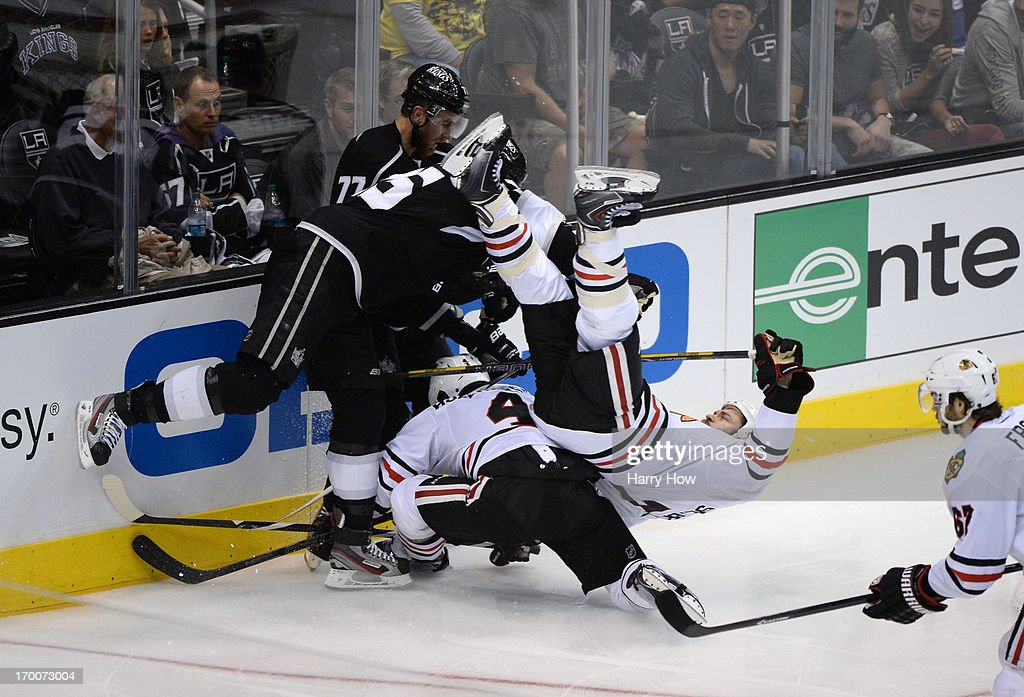 <a gi-track='captionPersonalityLinkClicked' href=/galleries/search?phrase=Dustin+Penner&family=editorial&specificpeople=589919 ng-click='$event.stopPropagation()'>Dustin Penner</a> #25 of the Los Angeles Kings checks <a gi-track='captionPersonalityLinkClicked' href=/galleries/search?phrase=Brent+Seabrook&family=editorial&specificpeople=638862 ng-click='$event.stopPropagation()'>Brent Seabrook</a> #7 of the Chicago Blackhawks near the end boards in the third period of Game Four of the Western Conference Final during the 2013 NHL Stanley Cup Playoffs at Staples Center on June 6, 2013 in Los Angeles, California.