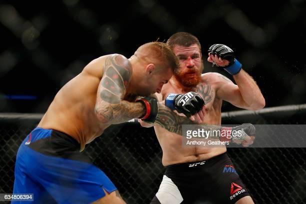 Dustin Poirier of United States exchanges punches with Jim Miller of United States in their lightweight bout during UFC 208 at the Barclays Center on...