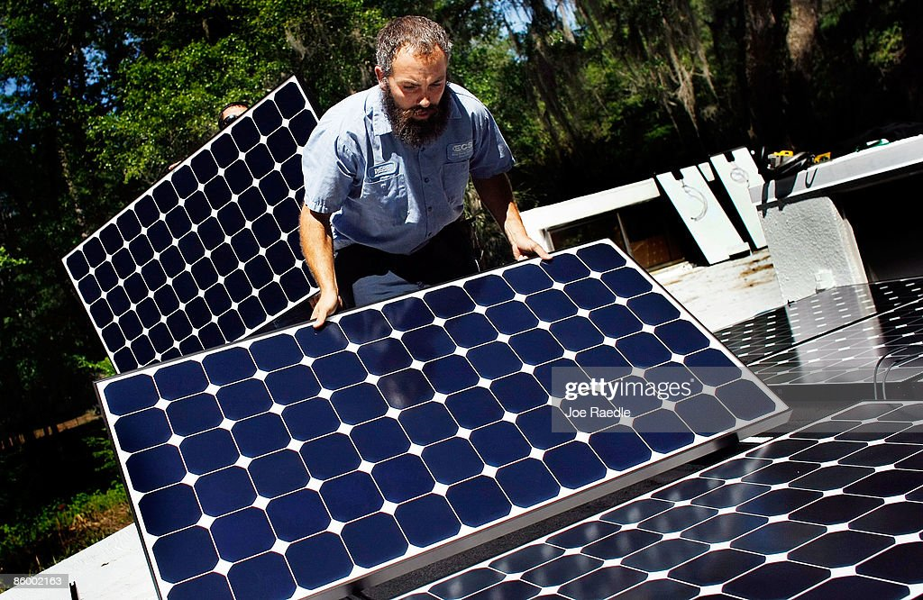 Dustin Rodgers, who works for ECS Solar Energy Systems, Inc, installs a solar panel system on the roof of a home on April 16, 2009 in Gainesville, Florida. Recently the city of Gainesville through a program initiated by the local Gainesville Regional Utilities became the first city in the nation to have a solar feed-in tariff ordinance, which means owners of new solar photovoltaic systems will be eligible to receive 32 cents per kilowatt hour of electricity produced by the system over the next 20 years. The new program has produced a spurt of solar installation projects around the city. Other states and cities around the nation are eyeing the feed-in tariff program as a renewable energy program they might be interested in doing.