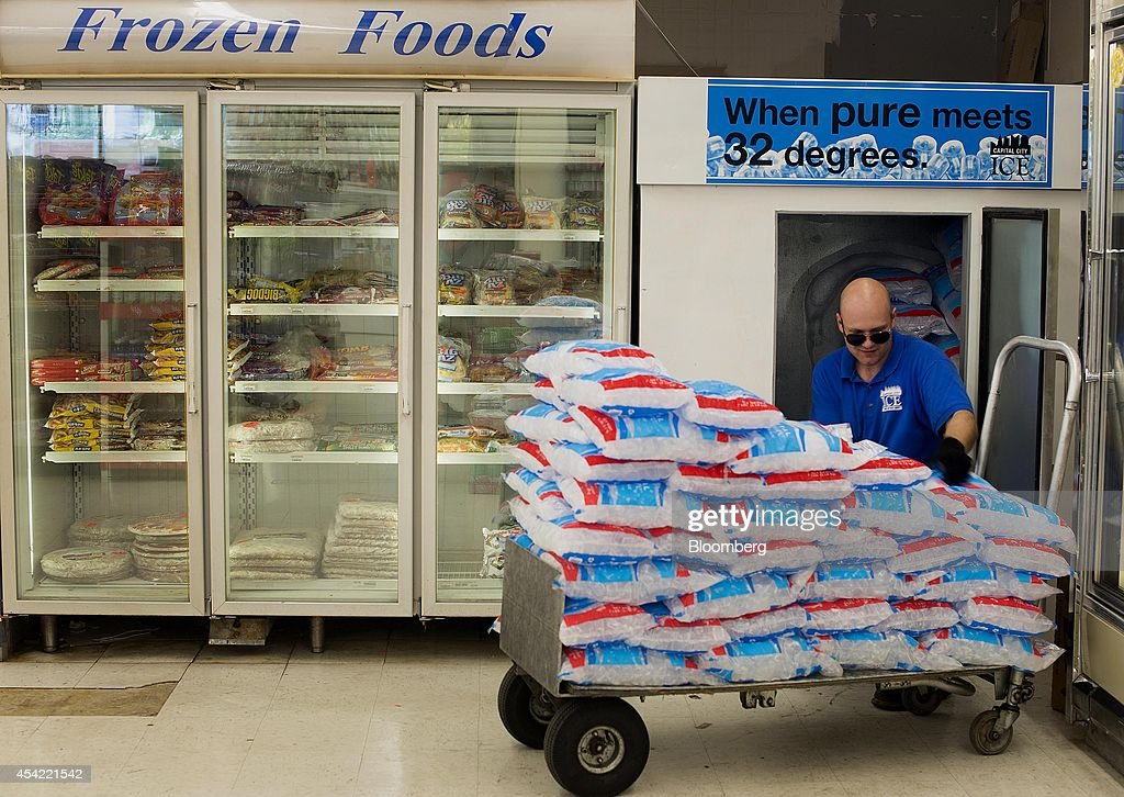 Dustin Stargel, delivery driver for Capital City Ice, stacks a cooler with bags of ice at a Shop 'n Save grocery store in Columbus, Ohio, U.S., on Tuesday, Aug, 26, 2014. The Institute for Supply Management (ISM) is scheduled to release U.S. manufacturing figures on Sept. 2. Photographer: Ty Wright/Bloomberg via Getty Images
