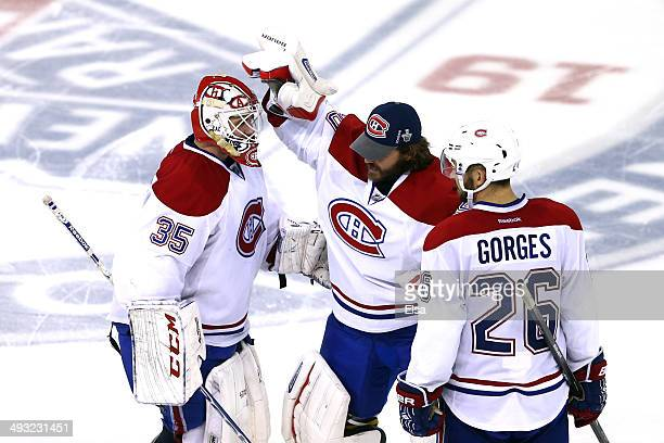 Dustin Tokarski of the Montreal Canadiens celebrate with teammates Peter Budaj and Josh Gorges after defeating the New York Rangers in overtime...