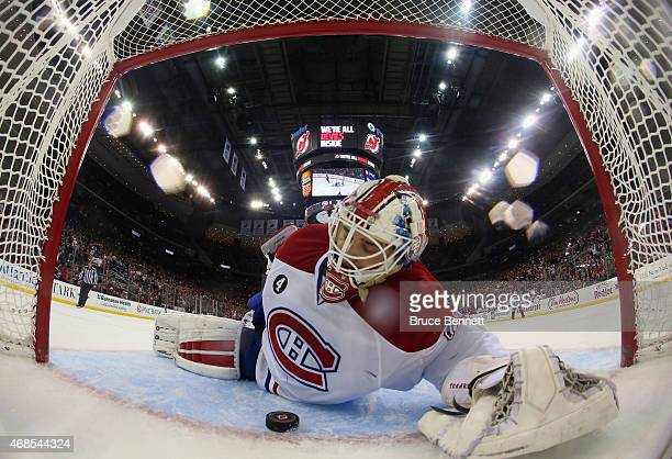 Dustin Tokarski of the Montreal Canadiens lies on the ice following a shootout goal by Patrik Elias of the New Jersey Devils at the Prudential Center...