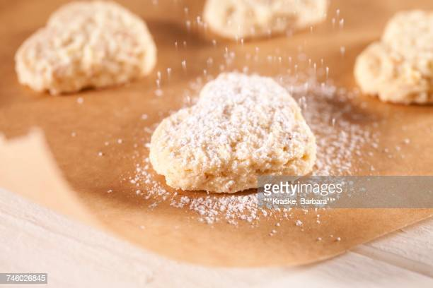 Dusting heart-shaped biscuits with icing sugar