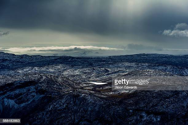 A dusting of snow covers barren and inhospitable mountain peaks on a highland tundra plateau.