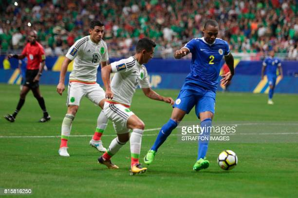 Dustley Mulder of Curacao competes for the ball with Elias Hernandez of during a Group C match between Mexico and Curacao as part of CONCACAF Gold...