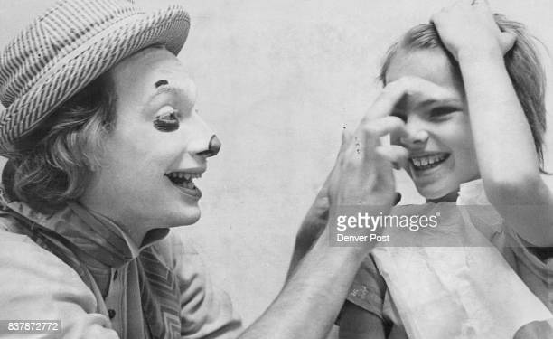 YOUNGSTERS 'Dusty' a genuine circus clown turns Donna Hines of 6727 Race St into a miniature replica of himself above as part of clown makeup classes...