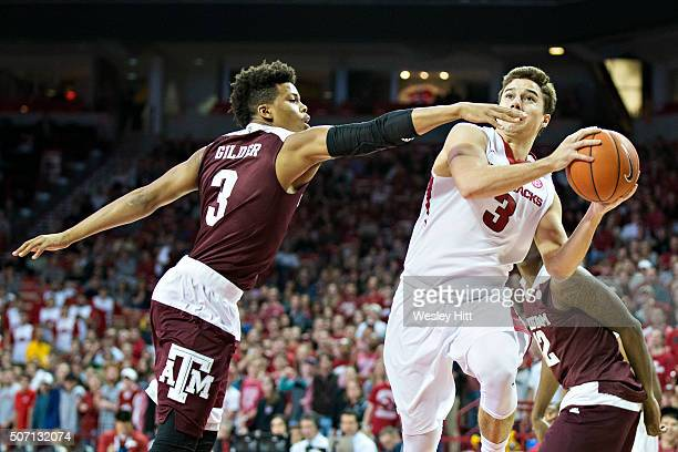 Dusty Hannahs of the Arkansas Razorbacks drives to the basket in the first half against Admon Gilder of the Texas AM Aggies at Bud Walton Arena on...