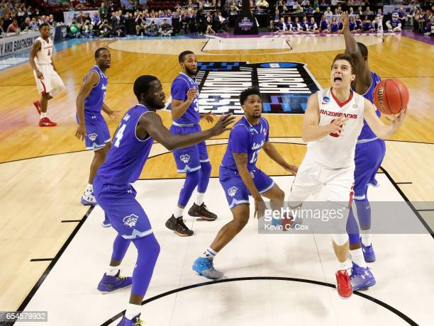 Dusty Hannahs of the Arkansas Razorbacks goes up for a shot against Ismael Sanogo of the Seton Hall Pirates in the first round of the 2017 NCAA Men's...