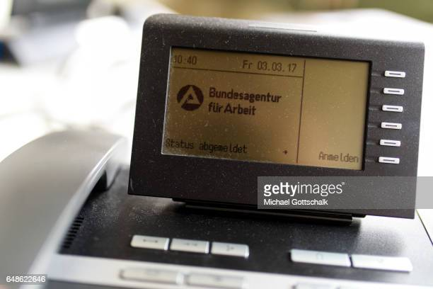 A dusty phone on a desk in Arbeitsagentur or employment Agency of German Federal Government with a display showing Status abgemedet or status log off...
