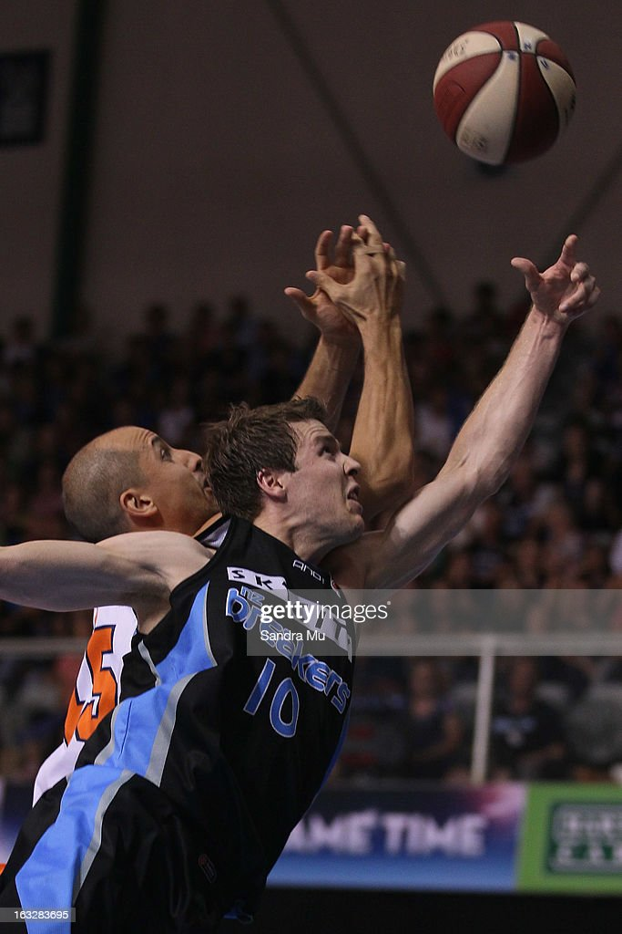 Dusty Rychart of the Titans and Tom Abercrombie of the Breakers stretch for the ball during the round 22 NBL match between the New Zealand Breakers and the Cairns Taipans at North Shore Events Centre on March 7, 2013 in Auckland, New Zealand.